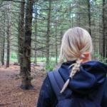 Frau blickt in Wald